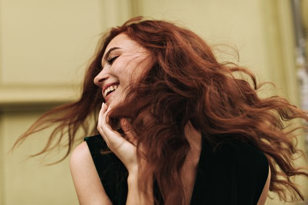 Curly,Woman,Posing,Outside,And,Laughing