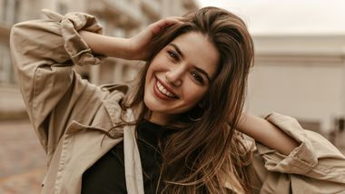 Cute,Cheerful,Lady,In,Black,Top,And,Trench,Coat,Smiles