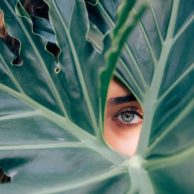 Frau hinter Pflanze
