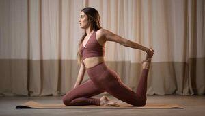 Frau macht in nachhaltiger Sportmode Yoga