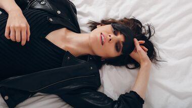 Frau mit Maske im Bett