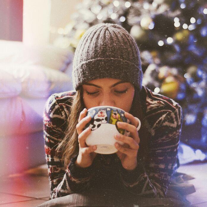 Frau mit Tasse vor Weihnachtsbaum