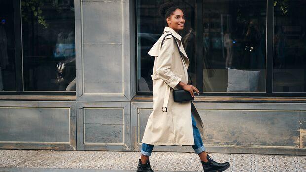 Frau trägt Trenchcoat