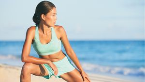Healthy,Active,Lifestyle,Woman,Stretching,Legs,Before,Running,On,Beach