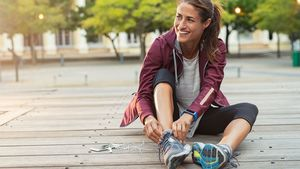Mature,Fitness,Woman,Tie,Shoelaces,On,Road.,Cheerful,Runner,Sitting