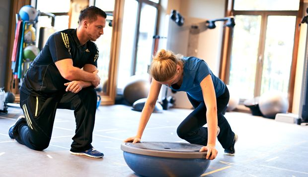 Trainer Adem zeigt Jessica eine Übung mit dem Bosu-Ball