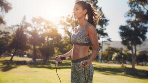Trainierte Frau in Sport-BH springt bei Sonnenschein Seil