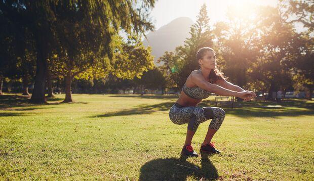 Trainierte Frau in Sport-BH springt bei Sonnenschein Seil in der Natur